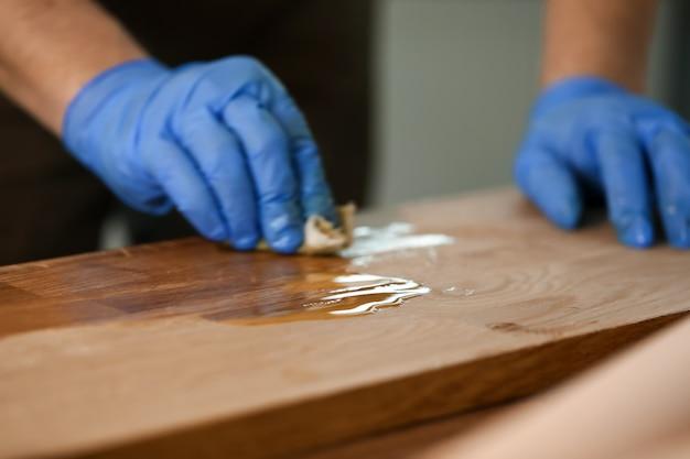 Mężczyzna lakieruje stół przy warsztatem