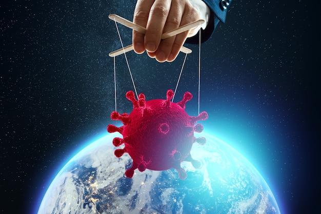 Mężczyzna lalkarz ręcznie wątku koronawirusa na tle ziemi. pojęcie rządu cieni, spisku światowego, manipulacji, kontroli.