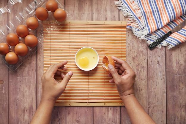 Mężczyzna łamiący jajko i wlewający do małego pojemnika na stole