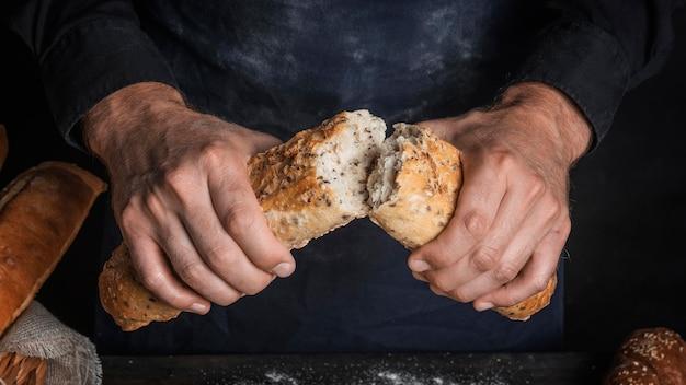 Mężczyzna łamie bochenek chleba