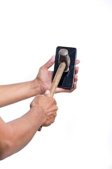 Mężczyzna łamie smartfon dużym młotkiem