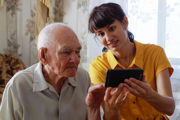 Mężczyzna lat 90. z dorosłą wnuczką siedzący razem na wygodnej kanapie z telefonem w rękach