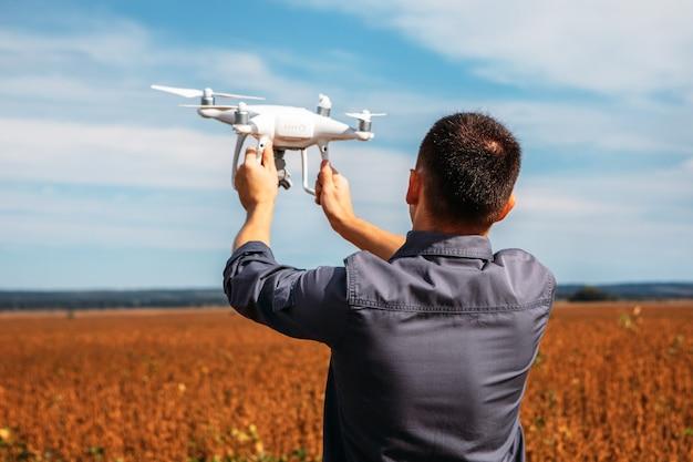 Mężczyzna latający dronem w żółtym polu