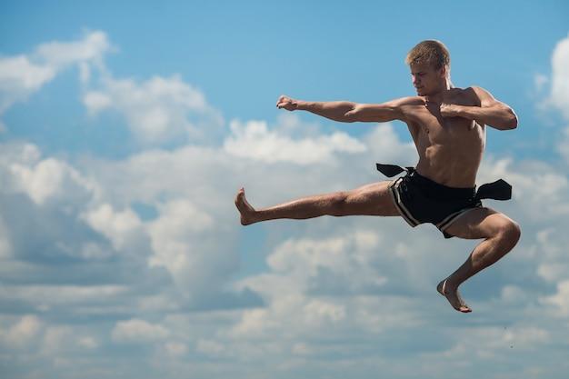 Mężczyzna latający kopnięcie w tle nieba