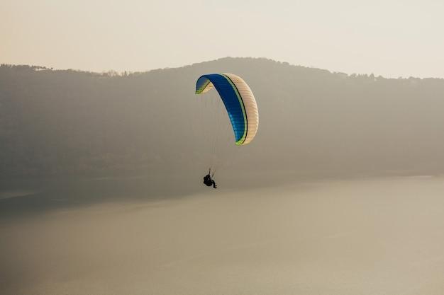 Mężczyzna latający z paralotnią.