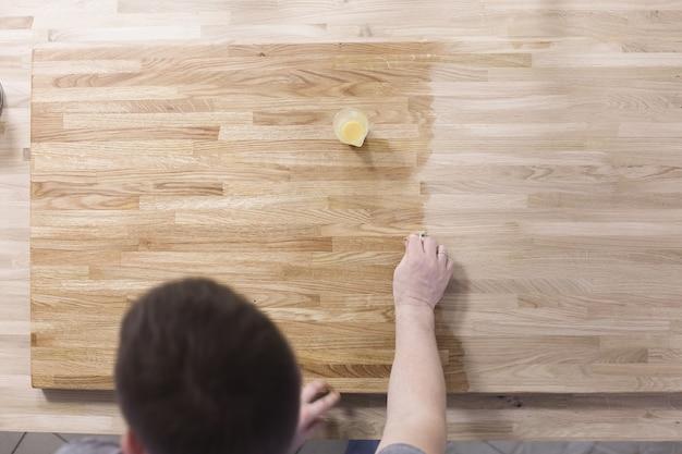 Mężczyzna leczy drewnianą powierzchnię stołu lakierem ochronnym