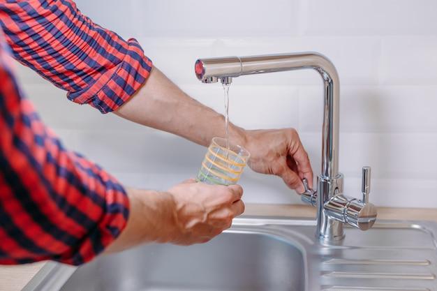 Mężczyzna leje szklankę wody z kranu z czystym filtrem w kuchni, z bliska