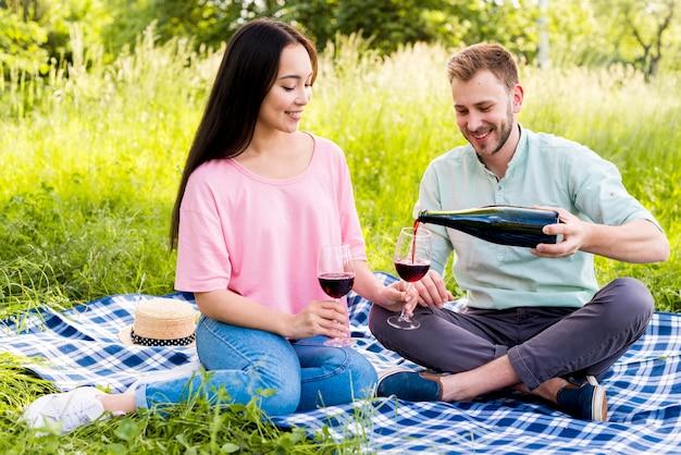 Mężczyzna leje wino dla dziewczyny