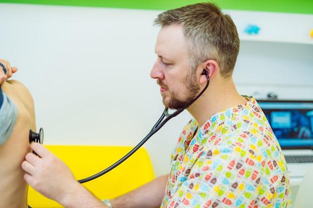 Mężczyzna lekarz bada małego chłopca za pomocą stetoskopu