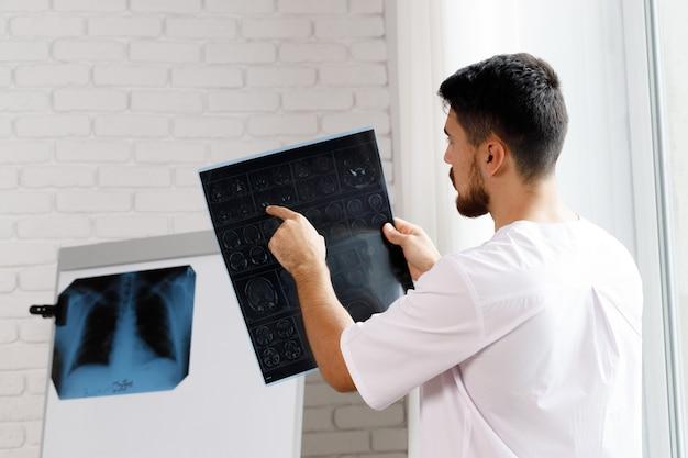 Mężczyzna lekarz bada rezonans magnetyczny mózgu pacjenta