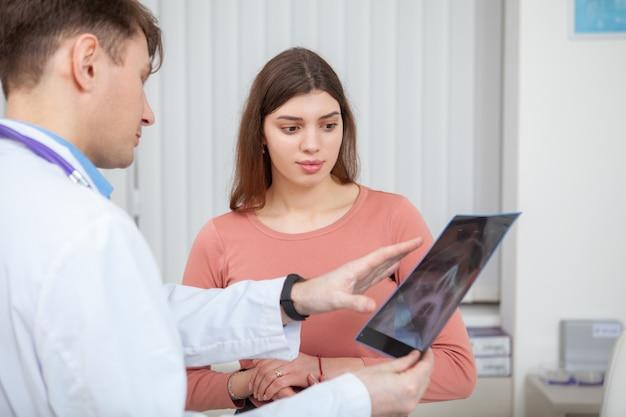 Mężczyzna lekarz bada rezonans magnetyczny swojej pacjentki