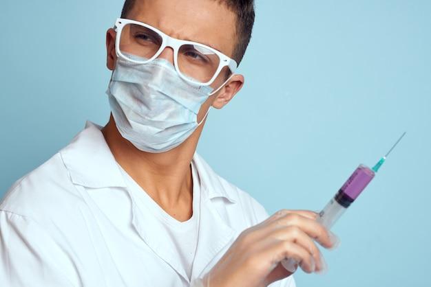 Mężczyzna lekarz biały fartuch leczenie instrumenty medyczne niebieskie tło