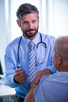 Mężczyzna lekarz daje zastrzyk dla pacjenta w szpitalu