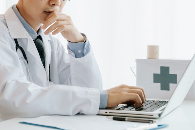 Mężczyzna lekarz korzysta z komputera, bada i analizuje, analizuje choroby i zapisuje informacje o pacjencie,