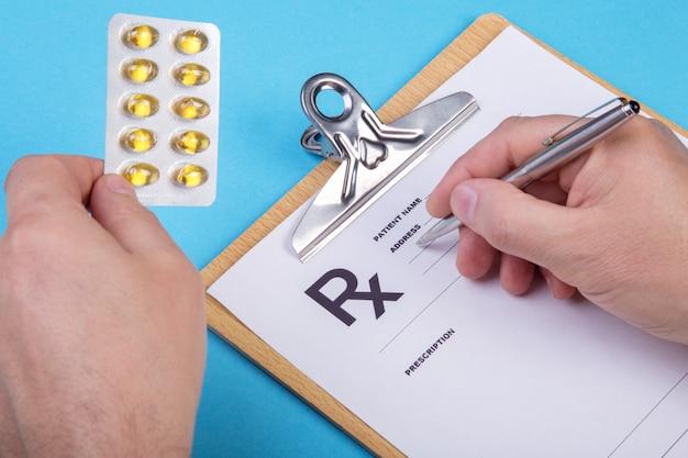 Mężczyzna lekarz lub farmaceuta trzymając w ręku słoik lub butelkę pigułek i pisania recepty na specjalnej formie.