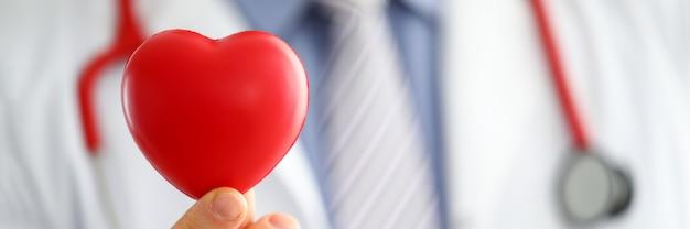 Mężczyzna lekarz medycyny ręce gospodarstwa i obejmujące czerwone zabawki serca