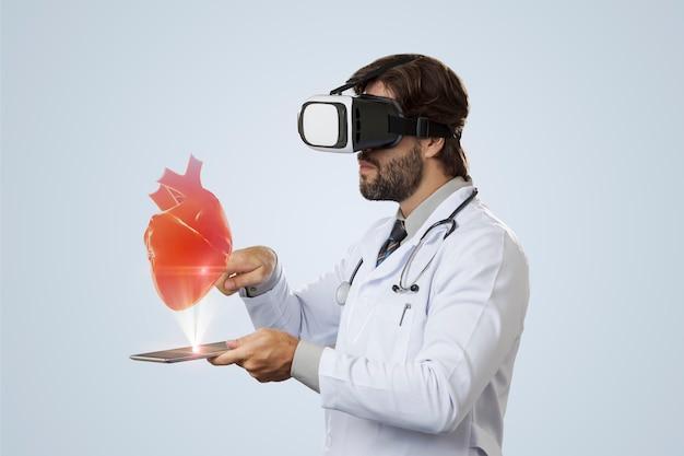 Mężczyzna lekarz na szarej ścianie przy użyciu okularów wirtualnej rzeczywistości, patrząc na wirtualne serce