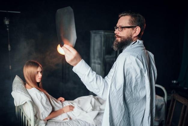 Mężczyzna lekarz patrząc na zdjęcie rentgenowskie chorej kobiety