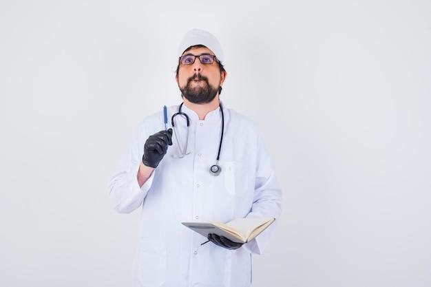 Mężczyzna lekarz pisze myśląc w białym mundurze, okularach i patrząc skoncentrowany, widok z przodu.
