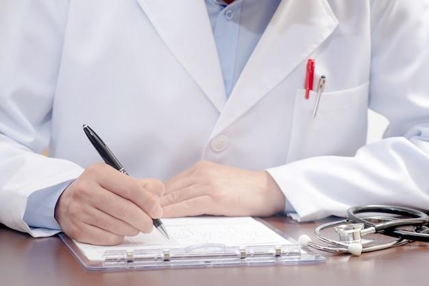 Mężczyzna lekarz pisze na formularzu medycznym ze stetoskopem w pobliżu.