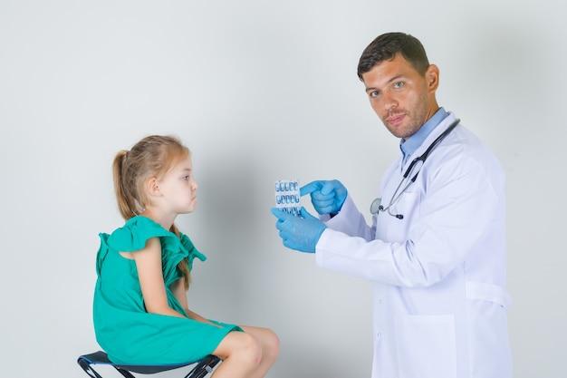 Mężczyzna lekarz pokazuje tabletki, podczas gdy dziecko siedzi wyczerpane w białym mundurze widok z przodu.