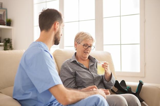 Mężczyzna lekarz pomaga starszej kobiecie biorąc jej lekarstwo na jej chorobę.