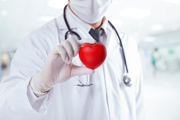 Mężczyzna lekarz posiadający kształt czerwonego serca. aby zachęcić lekarzy, aby zachęcić personel medyczny do przezwyciężenia covid 19. koncepcja opieki zdrowotnej i medycznej
