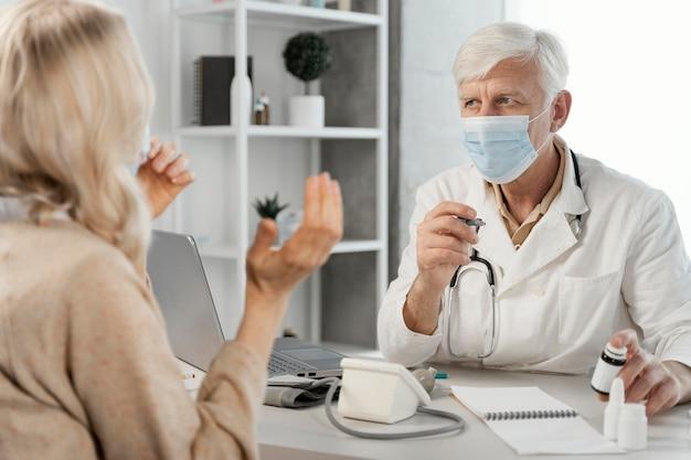 Mężczyzna lekarz przepisuje tabletki pacjentowi