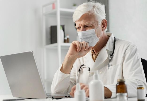 Mężczyzna lekarz przy biurku z lekami