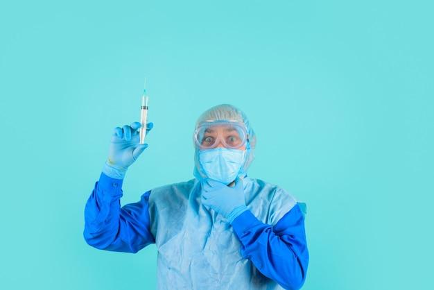 Mężczyzna lekarz przygotowujący się do wstrzyknięcia mężczyzna lekarz w masce z lekarzem strzykawką w kombinezonie ochronnym