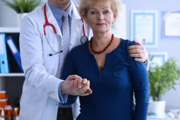 Mężczyzna lekarz przytulił starszą panią, pomagając wyjść