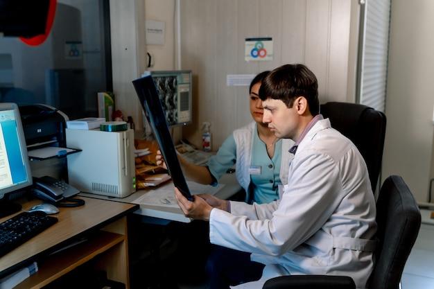 Mężczyzna lekarz radiolog siedzi z koleżanką w biurze. omówienie filmu mri. problemy medyczne.