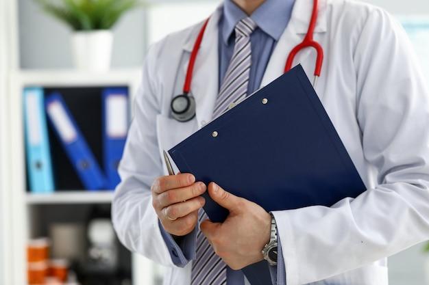 Mężczyzna lekarz ręka trzyma srebrny długopis wypełniający listę historii pacjenta w podkładce schowka.