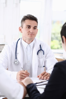 Mężczyzna lekarz rodzinny słucha uważnie młodych