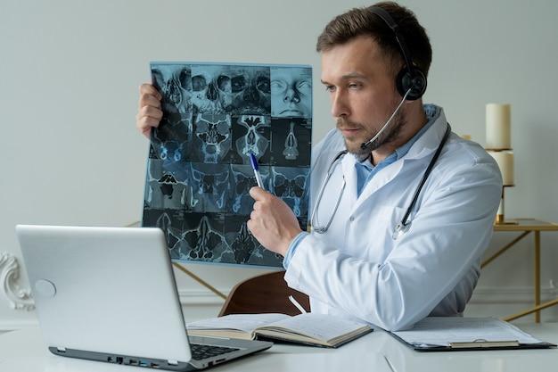 Mężczyzna lekarz słucha pacjenta podczas sesji telemedycznej lekarz mężczyzna po konsultacji online na laptopie z obrazem rentgenowskim i omawiania diagnozy