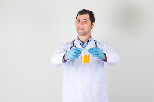 Mężczyzna lekarz trzyma szklankę soku w białym fartuchu, rękawiczkach i wygląda wesoło. przedni widok.