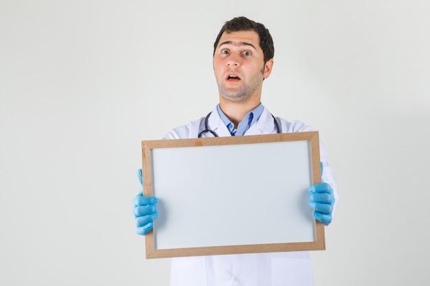 Mężczyzna lekarz trzymając białą tablicę w białym fartuchu, rękawiczkach i patrząc zszokowany, widok z przodu.