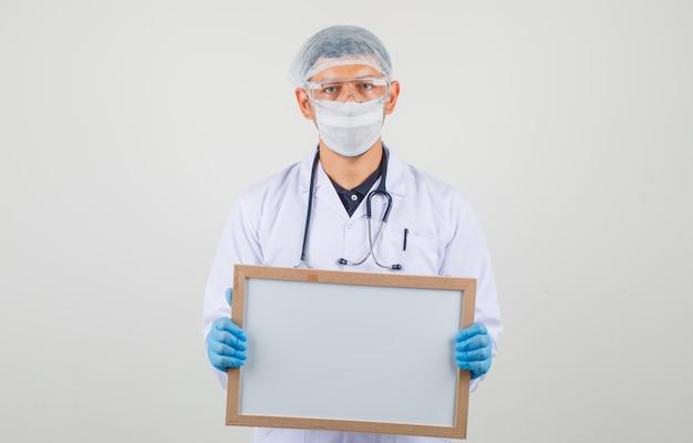 Mężczyzna lekarz trzymając białą tablicę w odzieży ochronnej i patrząc ostrożnie