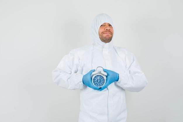 Mężczyzna lekarz trzymając budzik w kombinezonie ochronnym