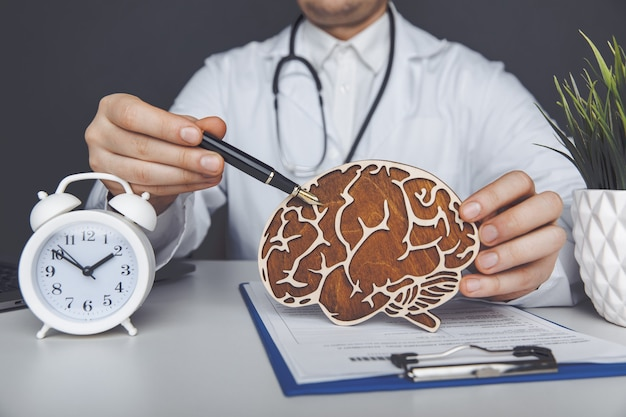 Mężczyzna lekarz trzymając drewniany mózg. znaczenie koncepcji wczesnej diagnozy.