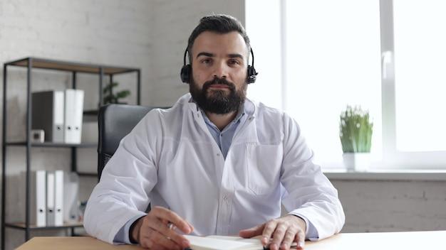 Mężczyzna lekarz ubrany w biały fartuch konsultuje pacjenta zdalnie online za pomocą zestawu słuchawkowego i kamery internetowej na laptopie.