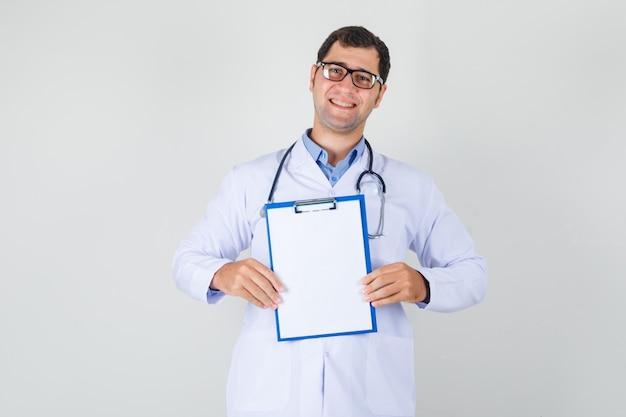 Mężczyzna lekarz w białym fartuchu, okulary trzymając schowek i patrząc wesoło