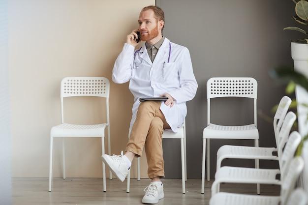 Mężczyzna lekarz w białym fartuchu siedzi na krześle rozmawia przez telefon komórkowy i przy użyciu komputera typu tablet podczas przerwy w szpitalu