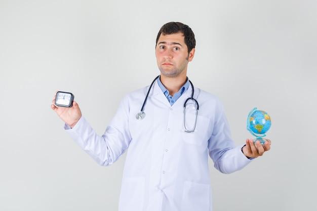 Mężczyzna lekarz w białym fartuchu trzyma światową kulę ziemską i zegar
