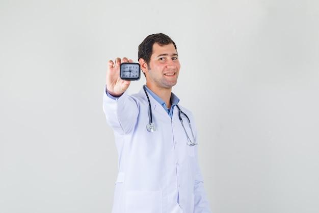 Mężczyzna lekarz w białym fartuchu, trzymając zegar i patrząc wesoło