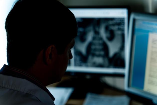 Mężczyzna lekarz w biurze pracy na komputerze. patrząc na zdjęcie rentgenowskie na monitorze. selektywne skupienie.