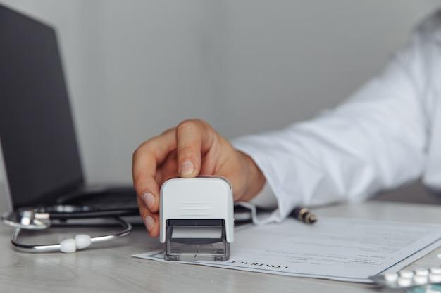 Mężczyzna lekarz w biurze stempluje dokument medyczny. koncepcja medycyny i opieki zdrowotnej