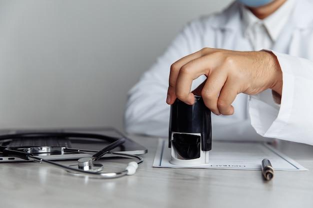 Mężczyzna lekarz w biurze stempluje dokument medyczny, zbliżenie ręki. koncepcja medycyny
