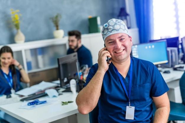 Mężczyzna lekarz w biurze uśmiecha się do kamery. nowoczesny szpital biurowy tło.