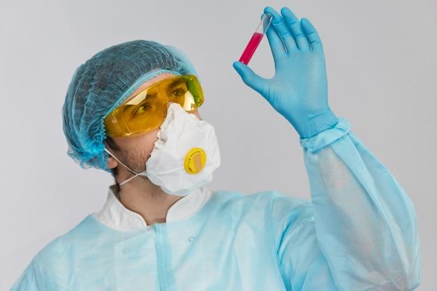 Mężczyzna lekarz w kombinezonie chroniącym przed zagrożeniem biologicznym sprawdza probówkę z różowym płynem